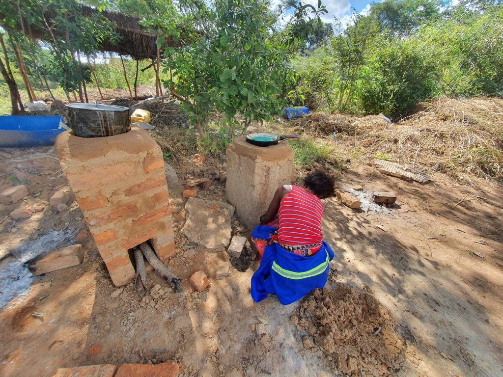 Woman Bending to Light Clay Stove